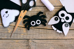 Halloween felt ornaments. Felt ghost, spider, owl ornaments on a vintage wooden table. Sewing craft tools and materials Royalty Free Stock Photography