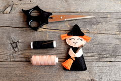 Halloween felt witch with broom, beige and black thread, needle, scissors on old wooden background. Tutorial. Step. Top view Stock Images