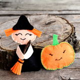 Halloween felt witch doll and pumpkin head near the stump. Wooden background Royalty Free Stock Images