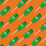 Halloween festive seamless pattern with cream cakes. Vector illustration with cream cakes in the form of frankenstein. Top view on sweets on orange backdrop Stock Images