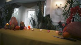Halloween. Festive table for Halloween. Halloween. Magic table for Halloween. Burning candles, pumpkins, knives and fruits on the magic table. The camera moves stock footage