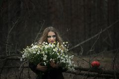 Halloween. field chamomile. beautiful girl in a black dress in the forest. royalty free stock image