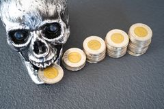 Halloween Skull With Stacks of Coins on display stock images