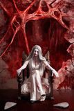 Halloween fine art portrait. Young vampire woman. Halloween fine art portrait of a beautiful young woman dressed as dark vampire in messy white dress seated at Stock Image