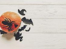 Halloween flat lay. jack lantern pumpkin with witch ghost bats a. Nd spider black decorations on white wooden background top view, space for text. seasonal Royalty Free Stock Images