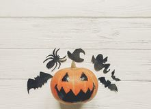Halloween flat lay. jack lantern pumpkin with witch ghost bats a. Nd spider black decorations on white wooden background top view, space for text. seasonal Stock Photos