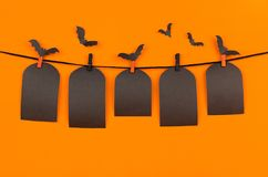 Halloween flock bats and black blank labels tomb hanging on clothespins, on orange background, mock up. Stock Photo