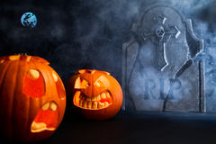 Halloween foggy night with pumpkins and tombstone. Angry face and scared face of Halloween pumpkins with tombstone, moon and misty dark background Royalty Free Stock Photos