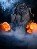 Halloween foggy night with pumpkins, tombstone, mo. Angry face and scared face of Halloween pumpkins with moon, tombstone and bat on misty dark background Stock Photos