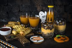 Halloween food assortment - sasage mummies, pumpkin dessert, gin. Halloween food. Scary sausage mummies, gingerbread cookies, pumpkin dessert and juice on dark stock image