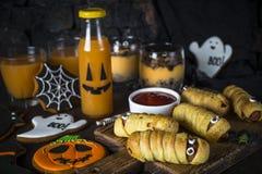 Halloween food assortment - sasage mummies, pumpkin dessert, gin. Halloween food. Scary sausage mummies, gingerbread cookies, pumpkin dessert and juice on dark royalty free stock images