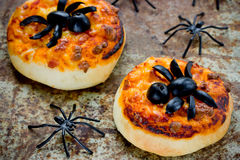 Halloween food background - funny mini pizza with olive spider stock images