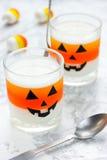 Halloween food idea: layered milk orange jelly in glasses on a w Stock Image
