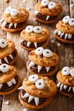 Halloween food: monsters of nutty cookies with chocolate cream c. Lose-up on the table. vertical royalty free stock photo