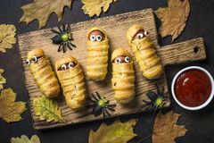 Halloween food. Scary sausage mummies in dough. Halloween food. Scary sausage mummies in dough baked with funny eyes with ketchup on dark background. Funny stock images