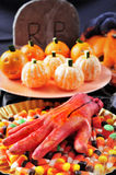 Halloween food. Some plates with different Halloween food, such as candies, mandarines as pumpkins, and scary ornaments such as an amputated hand or a grave Royalty Free Stock Photo