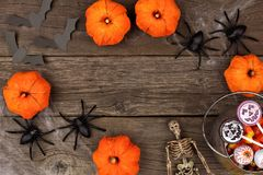 Halloween frame of pumpkin decor, spiderwebs and candy over wood Stock Photography