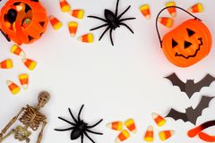 Halloween frame of scattered candy and decor over white stock image