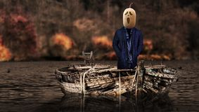 Halloween frightening pumpkin head ghost on a vessel floating in a scary landscape. Halloween a frightening pumpkin head ghost on a vessel floating in a scary stock photo