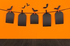 Halloween fun orange background with black blank sale labels and dark wooden board, mock up. Royalty Free Stock Photo