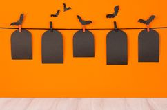 Halloween fun orange background with black blank sale labels and white wooden board, mock up. Stock Image