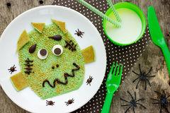 Halloween funny green monster spinach pancakes with chocolate. C. Reative breakfast for kids top view Royalty Free Stock Photo