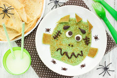 Halloween funny green monster spinach pancakes with chocolate. C. Reative breakfast for kids top view Royalty Free Stock Photography