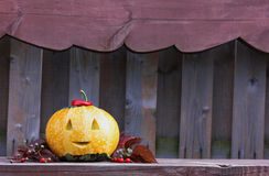 Halloween funny pumpkin with a smile in autumn leaves on wooden bench Royalty Free Stock Images