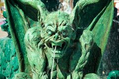 Halloween gargoyle. Green scary gargoyle with water falling around it royalty free stock photography
