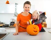 Halloween gekleed meisje met moeder die hefboom-o-Lantaarn voorbereiden Stock Foto