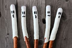 Halloween ghost, candy dipped pretzel rods on aged wood Stock Image