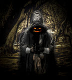 Halloween ghost in the forest. Background image of halloween ghost with scary jack face, in the hood in dark forest Stock Photo