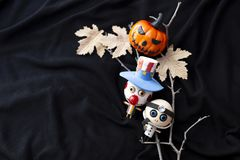 Halloween ghost wooden doll and funny Halloween pumpkin on dry branch and paper leaves on black background stock images