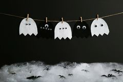 Halloween ghosts. Hanging on black background Royalty Free Stock Photos