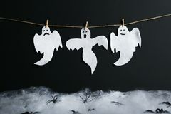 Halloween ghosts. Hanging on black background Stock Photos