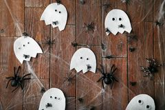 Halloween ghosts with spiders. On brown wooden table Stock Images