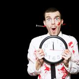 Halloween Ghoul Holding Clock Set To Midnight. Creepy Halloween Ghoul In Blood Stained Business Shirt And Tie Holding Clock Set To Midnight In A All Hallows Eve Royalty Free Stock Photos