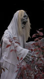 Halloween Ghoul on the Prowl. Ghoulish figure in white shroud on move. Skull face in full mouthed scream Stock Photo