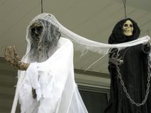 Halloween Ghouls. Halloween display of a female and male skeleton on a front porch to scare the children on Halloween stock photo