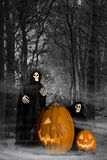 Halloween Ghouls in Forest. Ghostly ghouls with Halloween jack-o-lanterns inviting visitors into dark and misty forest for Halloween party. Jack-o-lanterns are Royalty Free Stock Photography