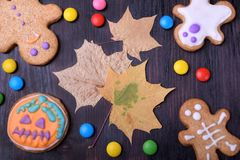 Halloween gingerbread cookies decorated with multicoloured glazing and dry maple leaves royalty free stock photos