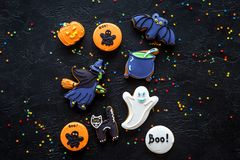 Halloween gingerbread cookies with pictures witch, cauldon and bat on black background top view copyspace. Bright halloween gingerbread cookies on black stock photo