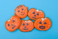 Halloween Gingerbread Faces. A pile of gingerbread in the shape of faces and pumpkins on blue background stock photography