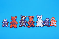 Halloween Gingerbreads. A row of multicolored painted gingerbread shapes on blue studio background Stock Images