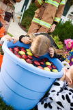 Halloween: Girl Bobbing For Apples. Group of neighborhood children on Halloween, having fun in costume trick-or-treating and playing games Royalty Free Stock Image