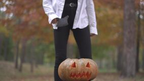 Halloween. Girl with a butcher`s knife coming to a pumpkin. Halloween holiday. All Saints` Night. Halloween concept stock video footage