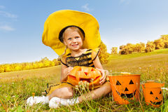 Halloween girl in costume of a bee sitting. On yellow grass with pumpkin and pail near her Stock Image