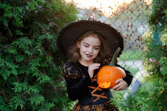 Halloween. The girl is dressed in dark dress and hat. Halloween. The girl is dressed in a dark dress and a hat. She holds orange pumpkin lamp in hand. The baby stock photo