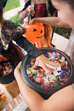 Halloween: Girl Grabs For Halloween Candy From Bucket Stock Photo