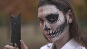 Halloween. Girl with Halloween make-up runs her finger along the blade of knife. Girl with Halloween make-up runs her finger along the blade of a knife stock footage